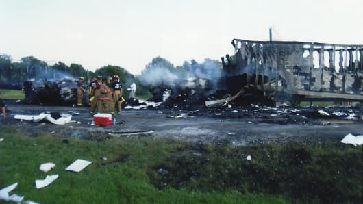 This photo shows the aftermath of the accident, including the burned out shell of a truck. The Lindner minivan was so crushed its wreckage cannot be seen.